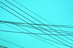Kreuzende Stromleitungen auf blauem Hintergrund Lizenzfreie Stockfotos