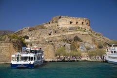 Kreuzfahrt zur Insel von Spinalonga Kleines Boot auf der blauen Lagune Spinalonga-Festung auf der Insel von Kreta, Griechenland stockfotografie