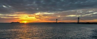 Kreuzschiff, das Verrazano-Enge-Brücke bei Sonnenuntergang führt Stockfoto
