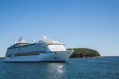 Kreuzschiff durch grüne Insel auf blauem Wasser Stockfotografie