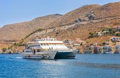 Kreuzschiff kommt den Hafen der Insel von Sym Lizenzfreie Stockfotografie