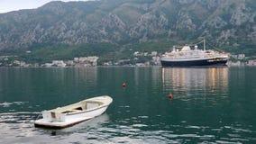 Kreuzschiff und ein Boot machten in der Bucht von Kotor, Montenegro fest lizenzfreies stockfoto