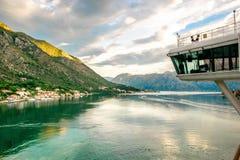 Kreuzschiffbrücke in Bucht Montenegros Kotor, die szenisches Dorf mit hohen Bergen während des Sonnenaufgangs betrachtet stockfoto