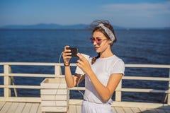 Kreuzschifffrau, die Handy auf Reiseferien in Ozean verwendet Mädchen simsende sms auf wifi an den tropischen Feiertagen stockbilder