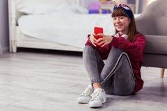 Kreuzungsbeine des entspannten Schulmädchens beim Sitzen auf Boden stockbilder