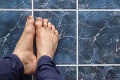 Kreuzungsfüße des jungen Mannes auf quadratischen Fliesen Adern in den Füßen sichtbar Stockbild