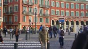 Kreuzungsstraße der Leute nahe rotem Gebäude von Caisse D'epargne Cote d'Azur stock video
