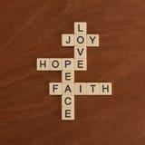 Kreuzworträtsel mit Wörter Glauben, Hoffnung, Liebe Kleines hölzernes Kruzifix, das auf braunem Hintergrund mit freiem Platz für  stockfotos