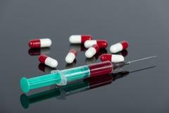 Krew wypełniał hypodermic igłę z luźnymi lek kapsułami na biurku Obraz Stock