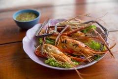 Krewetki, Piec na grillu rzeczna garnela lub Tajlandzka garnela na drewnianym tle, obraz royalty free