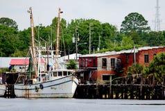 Krewetkowa łódź dokująca przy drewnianym molem fotografia stock