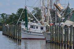 Krewetkowe łodzie cumować drewnianymi pilonami Zdjęcie Stock
