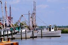 Krewetkowe łodzie cumować drewnianymi pilonami Fotografia Stock
