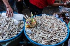 Krewetkowi sprzedawcy w tradycyjnych rynkach Badung sprzedawali garneli na tacy która poprzednio słuzyć canang jako błogosławieńs obraz stock