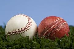 Kricket-Kugel und Baseball auf Gras mit blauem Himmel - Änderung geschehen Stockfotografie
