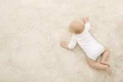 Kriechendes Baby auf Teppich-Hintergrund, Säuglingskinderdraufsicht, neugeboren stockbild