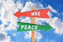 Krieg gegen Frieden auf hölzernem Richtungszeichen Stockfotos