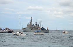 Kriegsschiff, welches das Yacht-Rennen ansieht Stockfotos