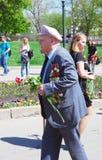Kriegsveteran geht mit Blumen Stockfoto