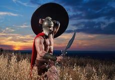 Krigare i det över huvudet hållande svärdet för hjälm Arkivbilder