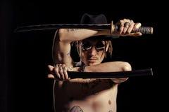 Krigare som poserar med svärdet med den tatuerade händer, halsen och bröstkorgen arkivbild