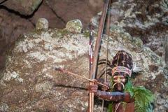 Krigaren av en Papuanstam av Yafi i traditionell kläder, prydnader och färgläggning Syften för forsar en bågskytt Royaltyfri Fotografi