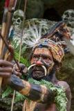Krigaren av en Papuanstam av Yafi i traditionell kläder, prydnader och färgläggning Syften för forsar en bågskytt Arkivbilder