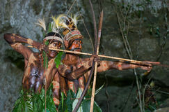 Krigarestam Yaffi i krigmålarfärg med pilbågar och pilar i grottan New Guinea ö Royaltyfri Fotografi