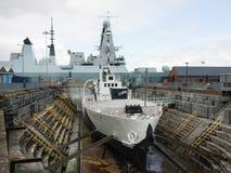 Krigsskepp M33 i drydock med HMS som är djärv i bakgrunden Royaltyfri Bild