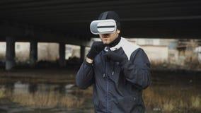 Krijgs in dozen doende mens in de hoofdtelefoon van VR 360 opleidingsstempels in virtuele werkelijkheidsstrijd bij stedelijke pla Stock Afbeelding