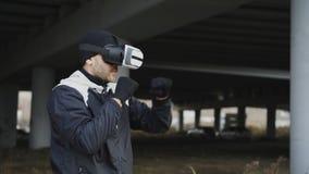 Krijgs in dozen doende mens in de hoofdtelefoon van VR 360 opleidingsstempels in virtuele werkelijkheidsstrijd bij stedelijke pla royalty-vrije stock afbeelding