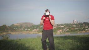 Krijgs in dozen doende mens in de hoofdtelefoon van VR 360 opleidingsstempels in virtuele werkelijkheidsstrijd bij stedelijke pla stock videobeelden