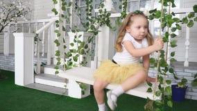 Krijgt de meisjes model gele rok op een rieten schommeling stock video