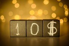 10$ krijt op zwarte kubussen op vage bokeh achtergrond wordt geschreven die royalty-vrije stock afbeeldingen