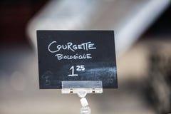 Krijtteken die organische courgettes onder de naam courgette verkopen biologique stock fotografie