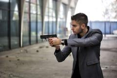 Kriminalare eller gangster eller polis som siktar ett skjutvapen Arkivfoto