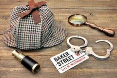 Kriminalare Hat, kikare och förstoringsapparat, teckenbagare Street och han royaltyfri bild
