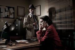 Kriminalare som intervjuar en ung eftertänksam kvinna i hans kontor arkivbild