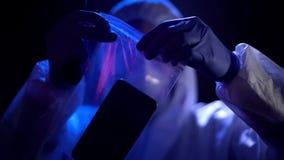 Krimineller Experte, der Smartphone mit kriminellen Fingerabdrücken in Plastiktasche einsetzt stockfoto