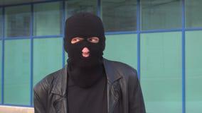 Krimineller Manndieb oder -räuber in der Maske macht lustige Gesichter im Kopfschutz stock video