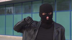 Krimineller Manndieb oder -räuber in der Maske zeigt Daumen unten stock video