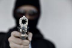 Krimineller Räuber mit dem Zielen des Gewehrs, Bösewicht in der Haube, die Pistole hält lizenzfreie stockfotografie