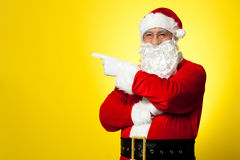 Kris Kringle gesturing towards the copy space area. Isolated against yellow background royalty free stock photography