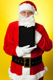 Kris Kringle presenting new updated tablet pc. Its for sale this Christmas stock images