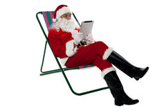Kris Kringle relaxing and using electronic tablet. Kris Kringle relaxing on chair and using electronic tablet. Isolated on white royalty free stock photography