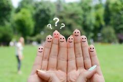 Krisenmetapher mit dem traurigen Finger zwischen lächelnden Fingern lizenzfreie stockbilder