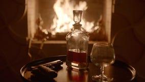 Kristalkaraf en het glas met whisky dichtbij de open haard op vooravond Pistool op de lijst stock video