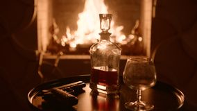 Kristalkaraf met whisky en het glas tegenover de open haard op vooravond Pistool op de lijst stock footage