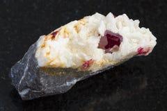 Kristall av Cinnabar i rå Carbonatite på mörker Arkivfoto