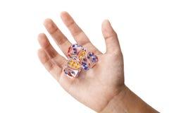 Kristall drei würfelt in der Kinderhand Stockfotografie